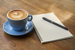 Write what you know with a notepad, pen and cup of coffee