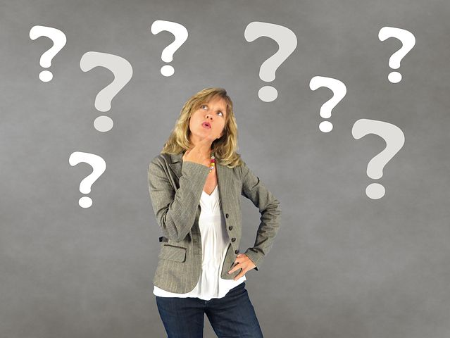 Pensive woman surrounded by question marks