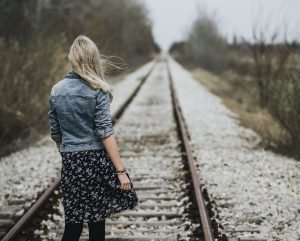 Woman standing on train track